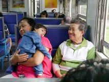 Aziatisch babymeisje die op haar tante` s schouder met haar grootmoederzitting naast tijdens een reis door trein leunen royalty-vrije stock foto's