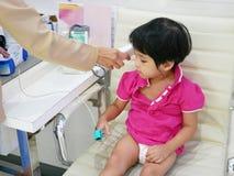 Aziatisch babymeisje die zuurstofbedrag in haar bloed, harttarief, en gemeten temperatuur hebben, gebruikend een oximeter en draa royalty-vrije stock afbeelding
