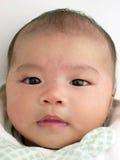 Aziatisch babyportret dat zacht glimlacht Stock Afbeeldingen