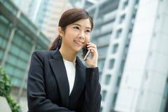Aziatisch bedrijfsvrouwenpraatje op mobiele telefoon Stock Foto's