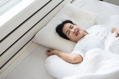 Aziatisch bejaarde die omdat gepast aan vermoeid van het werk, Vrouwelijke snor terwijl het slapen op bed snurken royalty-vrije stock foto's