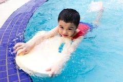 Aziatisch Chinees Little Boy die met Drijvende Raad zwemmen Royalty-vrije Stock Fotografie