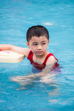 Aziatisch Chinees Little Boy die met Drijvende Raad zwemmen Stock Afbeelding