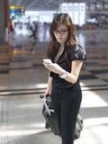 Aziatisch Chinees meisje dat haar telefoon controleert bij luchthaven royalty-vrije stock foto's
