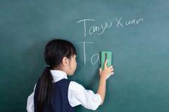 Aziatisch Chinees meisje die het groene bord afvegen stock foto