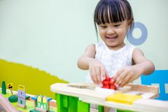 Aziatisch Chinees meisje die houten stuk speelgoed trein spelen stock foto
