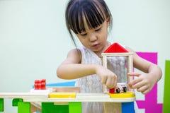 Aziatisch Chinees meisje die houten stuk speelgoed trein spelen stock fotografie