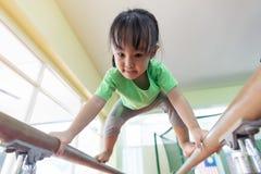 Aziatisch Chinees meisje die op brug beklimmen Stock Afbeelding