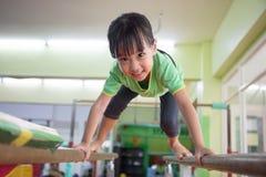 Aziatisch Chinees meisje die op brug beklimmen Stock Fotografie