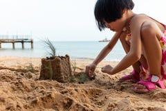 Aziatisch Chinees meisje het spelen zand bij strand royalty-vrije stock foto