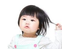 Aziatisch de aanrakingshaar van het babymeisje royalty-vrije stock afbeelding