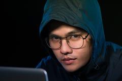 Aziatisch hakker het binnendringen in een beveiligd computersysteem computernetwerk met laptop in dark Cyber royalty-vrije stock foto's