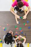 Aziatisch het Alfabetstuk speelgoed van het leraarsspel met studenten stock foto's