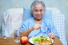 Aziatisch hoger of bejaard oud damevrouw geduldig het eten ontbijt stock fotografie