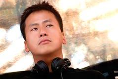 Aziatisch jong DJ zit ergens op en let stock fotografie