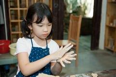 Aziatisch jong geitje dat aardewerk gestalte geeft Royalty-vrije Stock Afbeelding