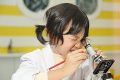 Aziatisch jong geitje dat microscoop onderzoekt Royalty-vrije Stock Fotografie