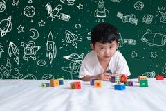 Aziatisch jong geitje die door met zijn verbeelding over wetenschap leren te spelen stock fotografie