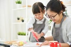 Aziatisch Jong geitje en jonge moeder die koekjes verfraaien stock afbeeldingen