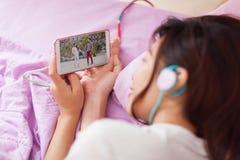 Aziatisch jong meisje die op mobiele video slimme telefoon letten Stock Afbeelding