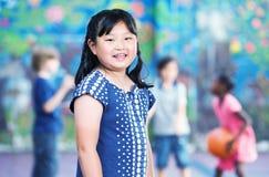 Aziatisch jong meisje die in schoolplein glimlachen terwijl andere jonge geitjes het spelen Stock Afbeelding