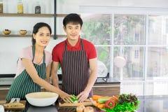 Aziatisch jong paar Bevinden zich glimlachend thuis het koken in de keuken royalty-vrije stock foto