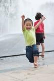 Aziatisch jongen en meisjesspel door fontein Stock Fotografie