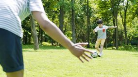 Aziatisch jongen het schoppen voetbal naar zijn vader als doelbewaarder in openlucht in de zomer in langzame motie stock footage