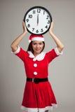 Aziatisch Kerstmismeisje in Santa Claus-kleren en klok bij midnigh stock afbeeldingen