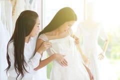 Aziatisch kijk vrouw het proberen op huwelijkskleding en het bijwonen door stylis stock fotografie