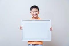 Aziatisch kind die en lege witte omlijsting tonen houden Royalty-vrije Stock Foto