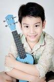 Aziatisch kind met zijn ukelele stock afbeelding