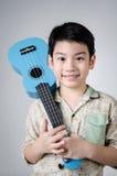 Aziatisch kind met zijn ukelele royalty-vrije stock afbeeldingen
