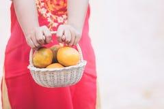 Aziatisch kindmeisje die de mand van sinaasappel houden Stock Fotografie