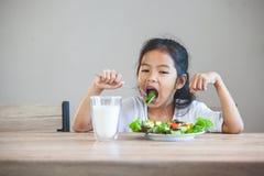 Aziatisch kindmeisje die gezonde groenten en melk voor haar maaltijd eten royalty-vrije stock afbeelding