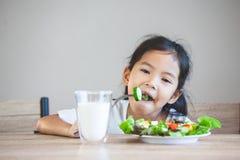 Aziatisch kindmeisje die gezonde groenten en melk voor haar maaltijd eten royalty-vrije stock fotografie