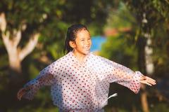 Aziatisch kindmeisje die regenjas dragen die pret met de regen in het zonlicht hebben te spelen royalty-vrije stock afbeelding