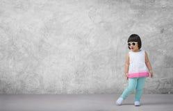 Aziatisch kindmeisje met concrete muurachtergrond in lege ruimte Stock Afbeelding