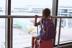 Aziatisch kindmeisje met rugzak die vliegtuig bekijken en op het inschepen in de luchthaven wachten royalty-vrije stock afbeelding