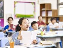 Aziatisch lage schoolmeisje die in klasse glimlachen stock foto