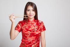 Aziatisch meisje in Chinese cheongsamkleding met eetstokjes royalty-vrije stock foto's