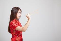 Aziatisch meisje in Chinese cheongsamkleding met eetstokjes stock afbeeldingen