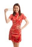 Aziatisch meisje in Chinese cheongsamkleding met eetstokjes stock fotografie