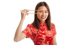 Aziatisch meisje in Chinese cheongsamkleding met eetstokjes stock foto's