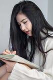 Aziatisch meisje dat nota's neemt Stock Afbeelding