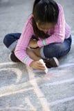 Aziatisch meisje dat op grond met stoepkrijt trekt stock afbeeldingen
