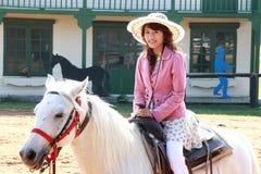 Aziatisch meisje dat wit paard berijdt. Royalty-vrije Stock Afbeelding