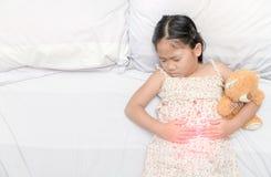 Aziatisch meisje die aan maagpijn lijden stock afbeelding