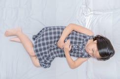 Aziatisch meisje die aan maagpijn op bed lijden royalty-vrije stock fotografie