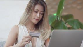 Aziatisch meisje die computer voor online aankoop met creditcard met behulp van stock afbeelding